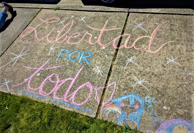"Sidewalk chalk: ""Libertad por todos"". In English: ""Liberty for all""."