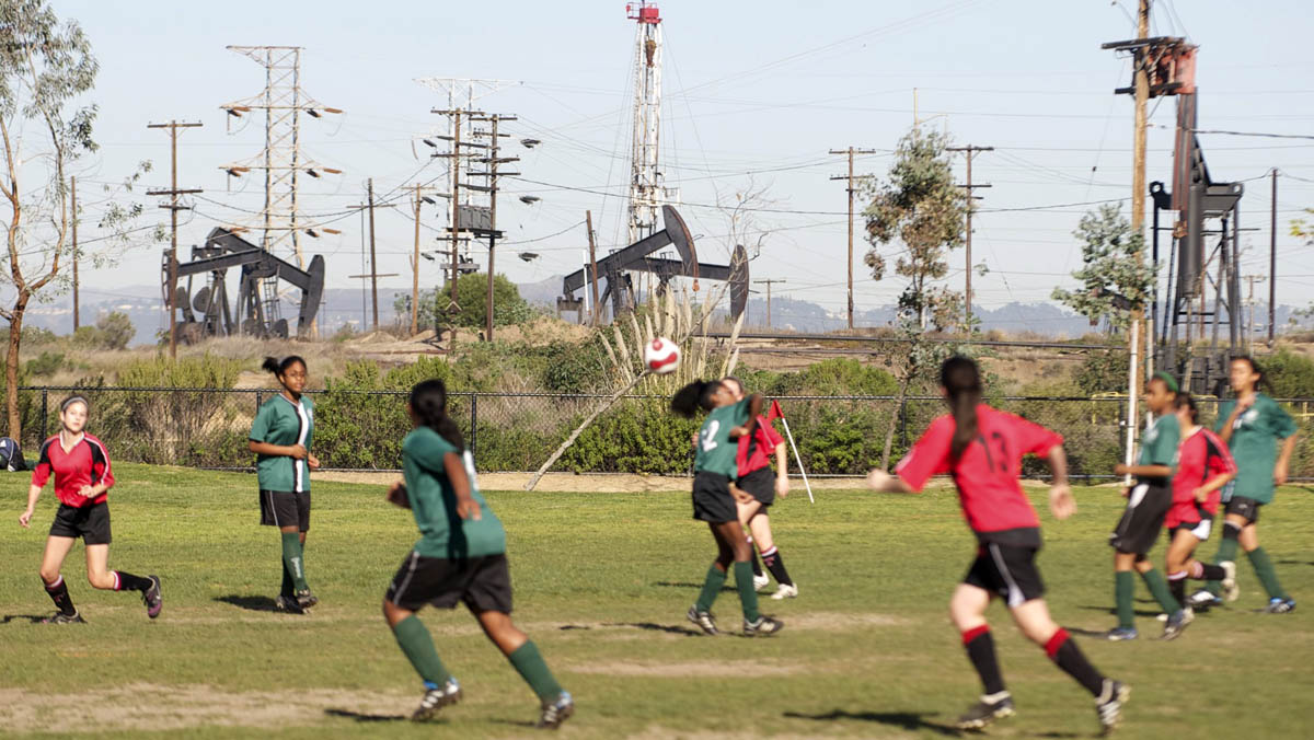 Oil rigs near children playing soccer