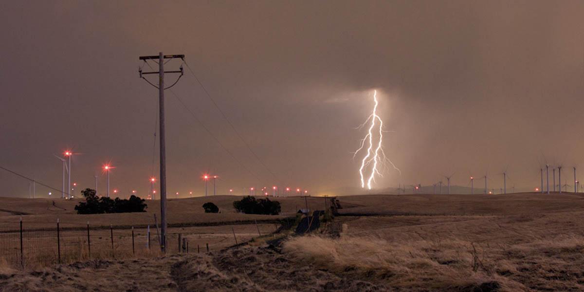 Power lines, wind farm and lightning