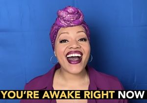 """Singer in a bright purple top, lipstick, and hair wrap with the words """"you're awake right now"""" highlighted below"""