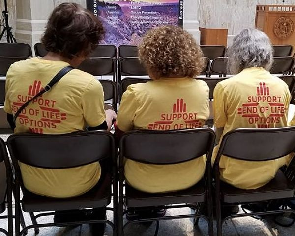 """Three advocates in yellow t-shirts that say """"Support end of life options"""""""