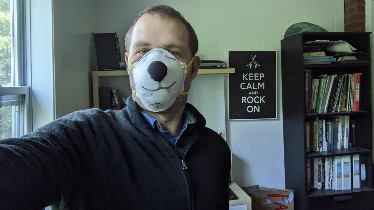 Eli wears a protective mask decorated to look like a polar bear in his home office.
