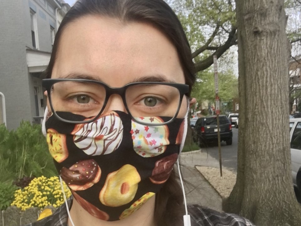 Susie wears a protective face mask made of fabric with images of donuts on it.