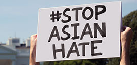 """a person holding a sign that says """"#stop asian hate"""""""