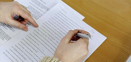 a person going over a document with a pen