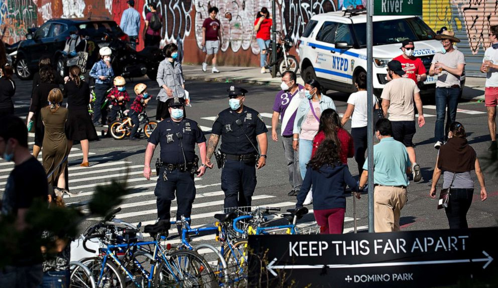 Photo shows two NYPD officer enforcing social distancing on a crowded street