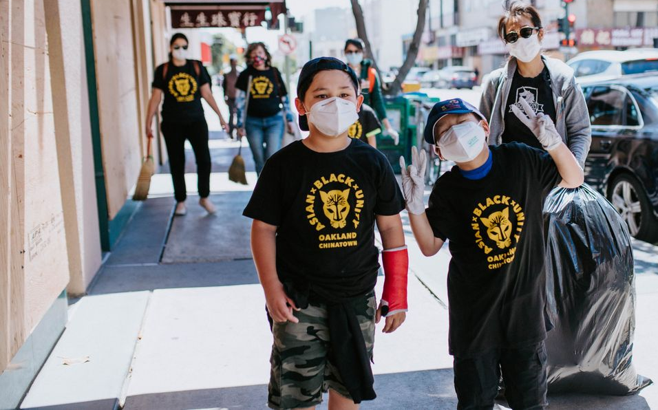 Two young Asian boys wearing shirts that say ''Asian-Black unity''