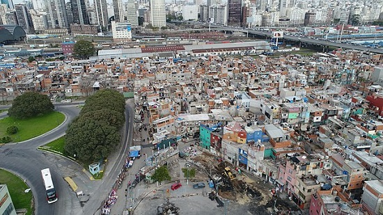 An aerial shot of a shantytown juxtaposed against office buildings.